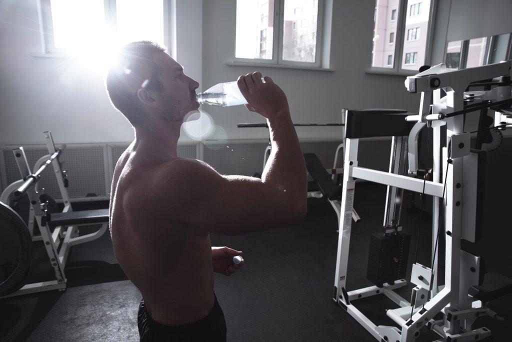 Muž pije vodu pred tréningom